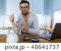 Bearded man having breakfast in the kitchen and 48641737