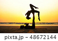 Fit sporty couple practicing acro yoga with partner together on the sandy beach. 48672144