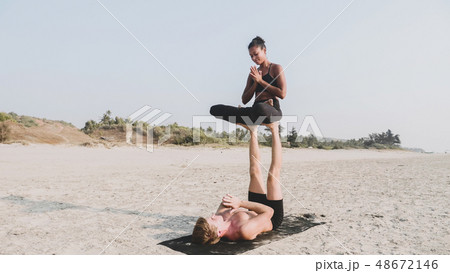 Fit sporty couple practicing acro yoga with partner together on the sandy beach. 48672146