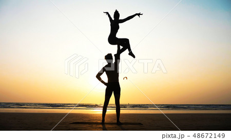 Fit sporty couple practicing acro yoga with partner together on the sandy beach. 48672149