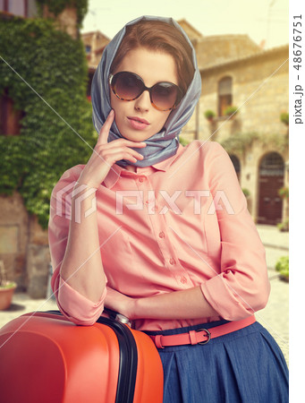 Elegant woman with a suitcase travel on street of 48676751