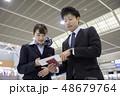 空港で航空券を見せて質問をするビジネスマン 48679764