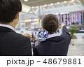 フライト時刻を教える空港スタッフと腕時計を見るビジネスマン 48679881