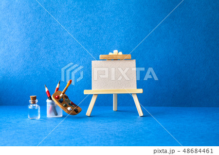 Wooden easel with textured blank paper canvas on blue background. Beautiful art class studio 48684461