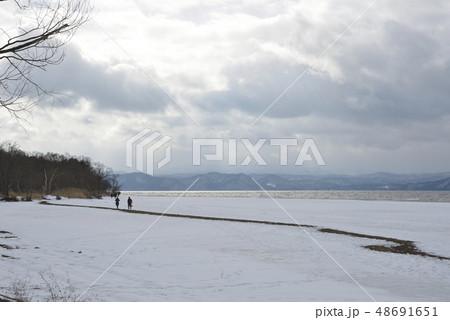 雪の猪苗代湖の湖畔を歩く人 48691651