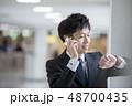空港で腕時計を見ながら通話するビジネスマン 48700435