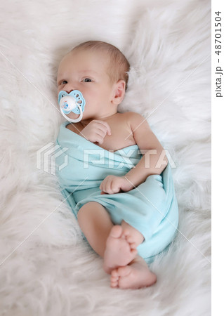 sleeping newborn baby wrapped in a blanket with a 48701504