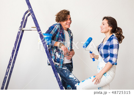 People, renovation and repair concept - Portrait of lovely couple doing redecoration in apartment 48725315
