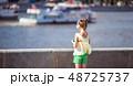 Little adorable girl listening music in the park 48725737