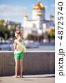 Little adorable girl listening music in the park 48725740