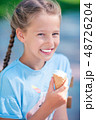 Little girl eating ice-cream outdoors at summer in outdoor cafe 48726204