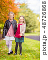 Little adorable girls at warm day in autumn park outdoors 48726868