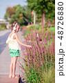 Little adorable girl listening music in the park 48726880