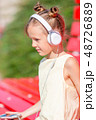 Little adorable girl listening music in the park 48726889