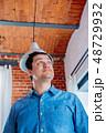Man in denim shirt keep head undr lamp  48729932