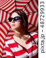 woman in sunglasses with red striped umbrella  48729933