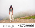 Beautiful happy young woman in mountains in the background of fog 48729966