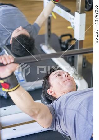 仕事帰りにトレーニングジムで真剣な表情でベンチプレスをするストイックな若い男性細マッチョサラリーマン 48768065