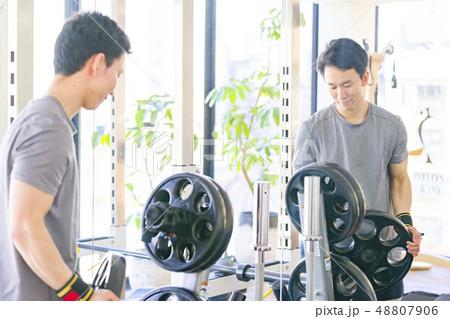 トレーニングジムのベンチプレス準備でバーベルウエイトをセッティングする真剣な眼差し目つきの男性本気 48807906