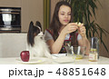Teen girl with dog Papillon prepare cookies, knead the dough 48851648