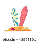 Two surfboards stand in the sand with a shell and a starfish. 48945301