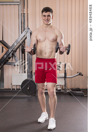 Young man flexing muscles with barbell in gym. 48948468