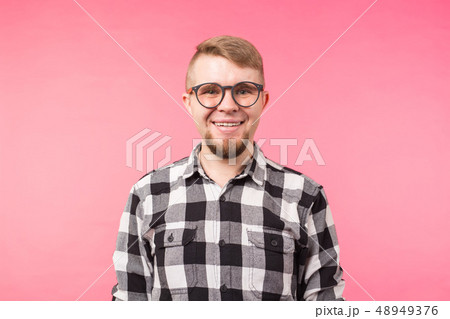 Portrait of a smiling bearded man in eyeglasses looking at camera isolated over pink background 48949376