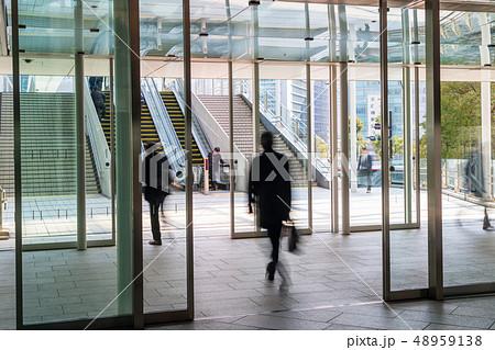 オフィス街 自動ドアを通るビジネスマン 48959138