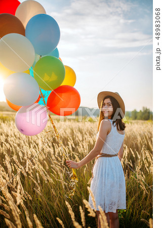 Girl with balloons walking in field, back view 48983068