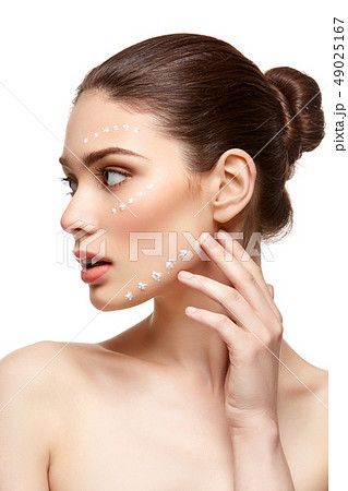 girl applying foundation on face isolated on white 49025167