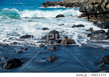 beautiful view on ocean water and black lava sand 49025174