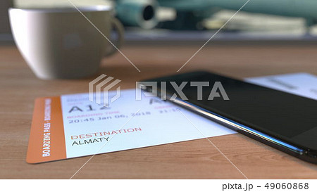 Boarding pass to Almaty and smartphone on the table in airport while travelling to Kazakhstan. 3D 49060868