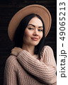 Indoor portrait of a young beautiful fashionable woman wearing hat and sweather. 49065213
