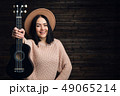 Portrait of country style girl posing with her small guitar on a chair 49065214
