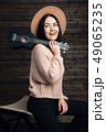 Portrait of country style girl posing with her small guitar on a chair 49065235