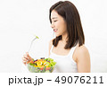 Portrait of a beautiful young Asian woman eating fresh salad fro 49076211