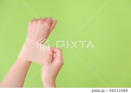写真素材:湿布を貼る手 しっぷ 貼る 治療 ボディケア 49211089