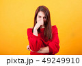 Image of beautiful young woman looking at the camera over yellow background 49249910