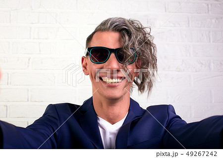 Portrait of stylish businessman with curly long hair in sunglasses smiling at the camera on white 49267242