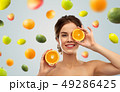 smiling woman with oranges over fruits background 49286425