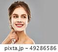 smiling young woman wearing sheet facial mask 49286586