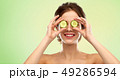 smiling woman with cucumber over green background 49286594