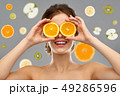 smiling woman with oranges on eyes over fruits 49286596