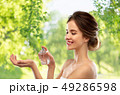 happy woman with perfume over gray background 49286598