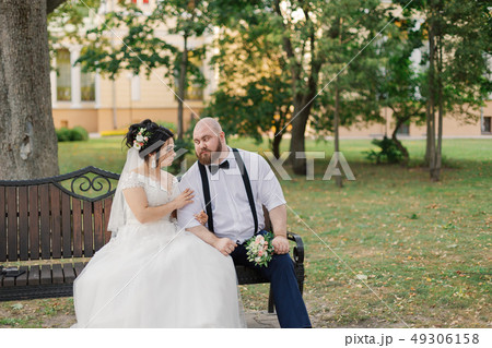 Newlyweds sit on a bench in the park. 49306158