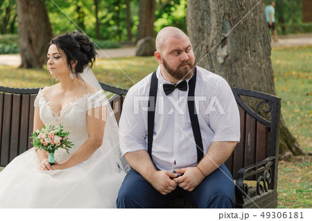 Newlyweds sit on a bench in the park. 49306181