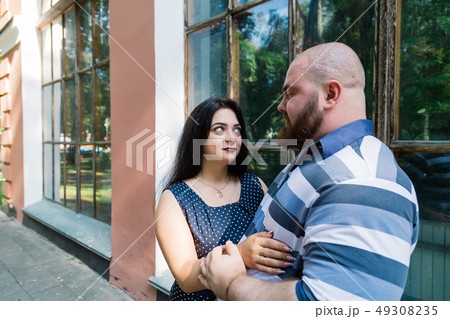 Two people in love stand hugging by large windows 49308235