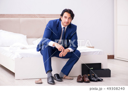 Young handsome businessman choosing shoes at home  49308240