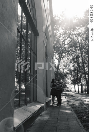 Two people in love stand hugging by large windows 49308249