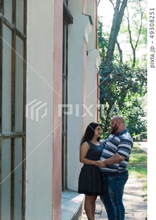 Two people in love stand hugging by large windows 49308251